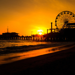 Photo of Santa Monica Pier sunset over the Pacific Ocean in Los Angeles County Southern California. Santa Monica Pier is a landmark that has an amusement park with a ferris wheel, roller coaster, restaurants, and other attractions.