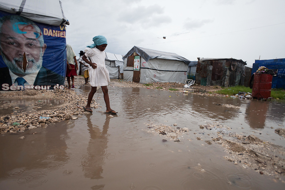 Joal Charles, 10, carefully traverses a puddle in the IDP camp where she lives on her way to collect clean water.