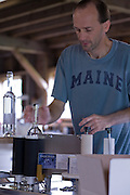 Keith Bodine labeling bottles of Back River Gin at Sweetgrass Winery, Union, Maine.