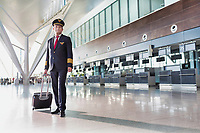 Portrait of mature pilot standing in check in area at airport