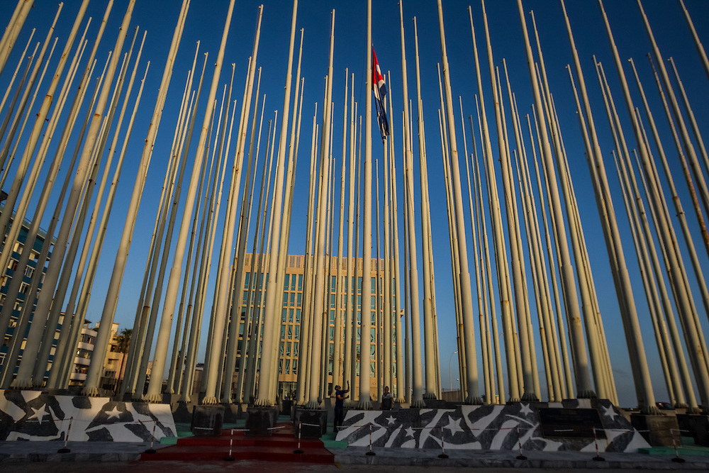 HAVANA, CUBA - JULY 20, 2015: Workers raise the Cuban flag in a plaza infront of the U.S. embassy. After more than half a century defined by mistrust and rancor, the United States officially reopened its six-story embassy in Havana today, marking a watershed moment of transition for the two countries as they lean toward closer diplomatic ties and ease past one of the last remnants of the Cold War.  President Barack Obama, when announcing an end to the diplomatic freeze, eased travel restrictions, opened the door for more remittances to Cuba and expanded the amount of goods that visiting Americans could bring back home – like Cuban cigars and rum. He even removed the country from the list of nations that sponsor terrorism. President Raul Castro, meanwhile, has spent the last five years, before the thaw even began with the Obama administration, attempting to alter his nation's economic dysfunction, ordering the firing of government employees, encouraging a slow but fresh influx of Cubans into self-employment and even creating a special economic zone in the coastal city of Mariel to attract foreign investment.  PHOTO: Meridith Kohut for The New York Times