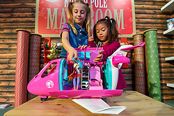 """© Licensed to London News Pictures. 13/11/2019. LONDON, UK. (L to R) Liana (aged 7) and Trilyna (aged 6) play with a Barbie Dreamplane Playset from Mattel at the preview of """"DreamToys"""", the official toys and games Christmas Preview, held at St Mary's Church in Marylebone.  Recognised as the countdown to Christmas, the Toy Retailer's Association, an independent panel of leading UK toy retailers, have selected the definitive and most authoritative list of which toys will be the hottest property this Christmas.  Photo credit: Stephen Chung/LNP"""