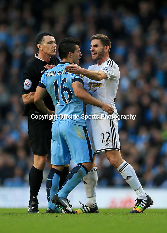 22nd November 2014 - Barclays Premier League - Manchester City v Swansea City - Referee Neil Swarbrick wades in to break up an argument between Sergio Aguero of Man City and Angel Rangel of Swansea - Photo: Simon Stacpoole / Offside.