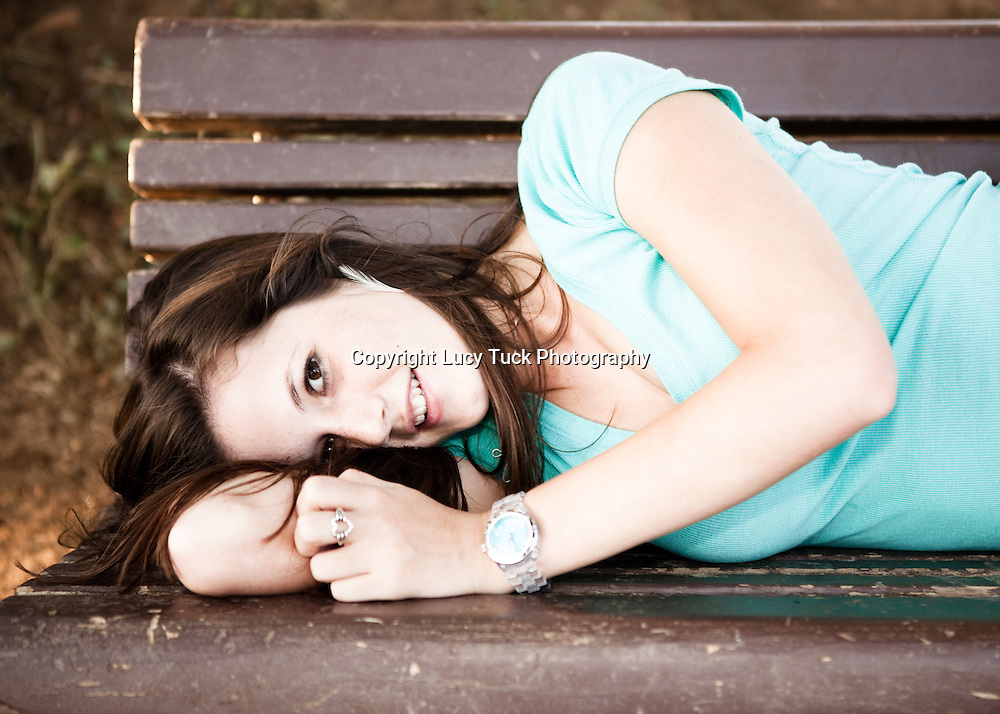 High School Senior Portrait of a girl lying on a bench, feather earring and turquoise top, Boulder, for Niwot High School near Longmont