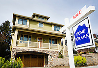 """A home with a """"For Sale"""" sign and """"Sold"""" sign."""