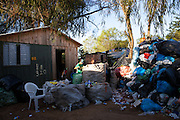 A young man sorts through a rubbish pile. <br /> <br /> There is a lot of  recycling of rubbish in the community surrounding the library.