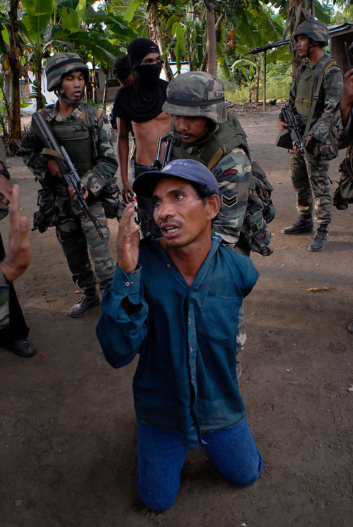 A man is arrested after a number of houses are burnt to the ground and a local man brutally attacked by a rival gang. A witness to the violence, his accuser, stands in the background, wearing a disguise to help him avoid retrobution. The arrested man was found with two vicous, handmade darts in his possession. Violence continues to plague Dili as continual clashes erupt between Easterners ( Lorosae) and Westerners (Loromonu) in Dili.