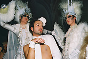 A man dances with two woman with large headdresses at Return to Narnia, Pushca, New Years Eve, 2004
