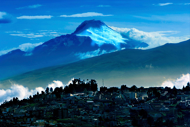 The high elevation of the city of Quito provides a dramatic view of the snow covered Cayambe Volcano, Ecuador's third highest peak, and the highest point in the world through which the equator directly passes.