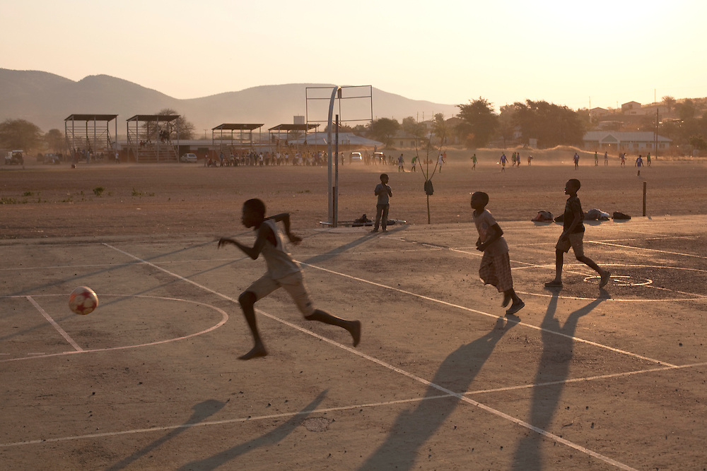 OPUWO, NAMIBIA: Kids playing football on a basketball court in Opuwo, Namibia.