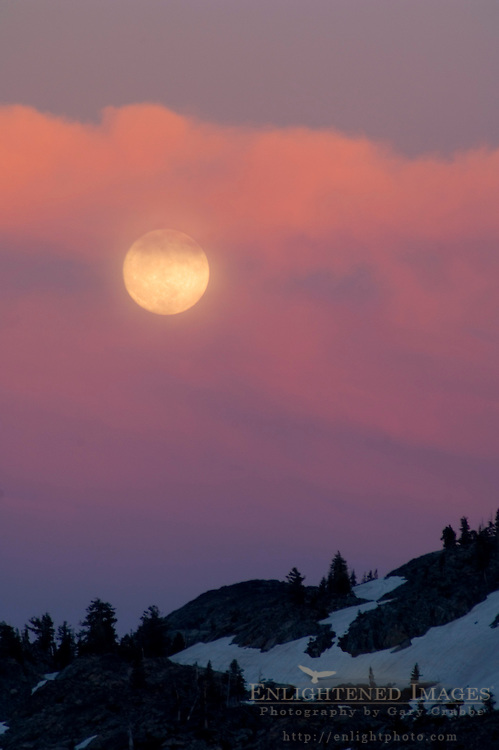 Full moon rising through storm clouds lit by alpenglow at sunset, Desolation Wilderness, El Dorado National Forest, California