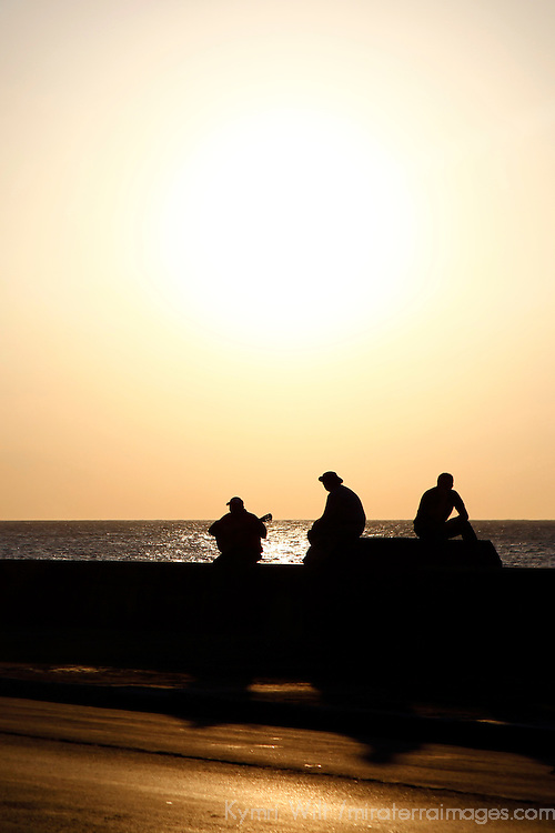 Central America, Cuba, Havana. Three Cubans and a guitar at sunset on the Malecon, Havana.
