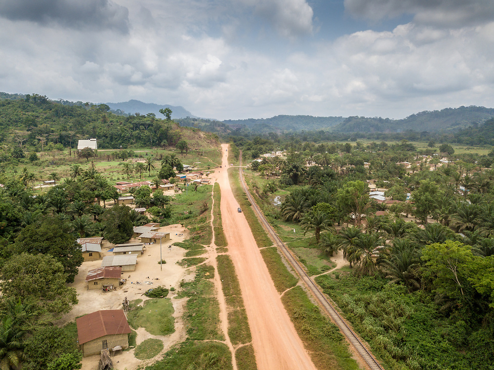 Aerial shot of a dirt road going through a town into the mountains in Ganta,Liberia