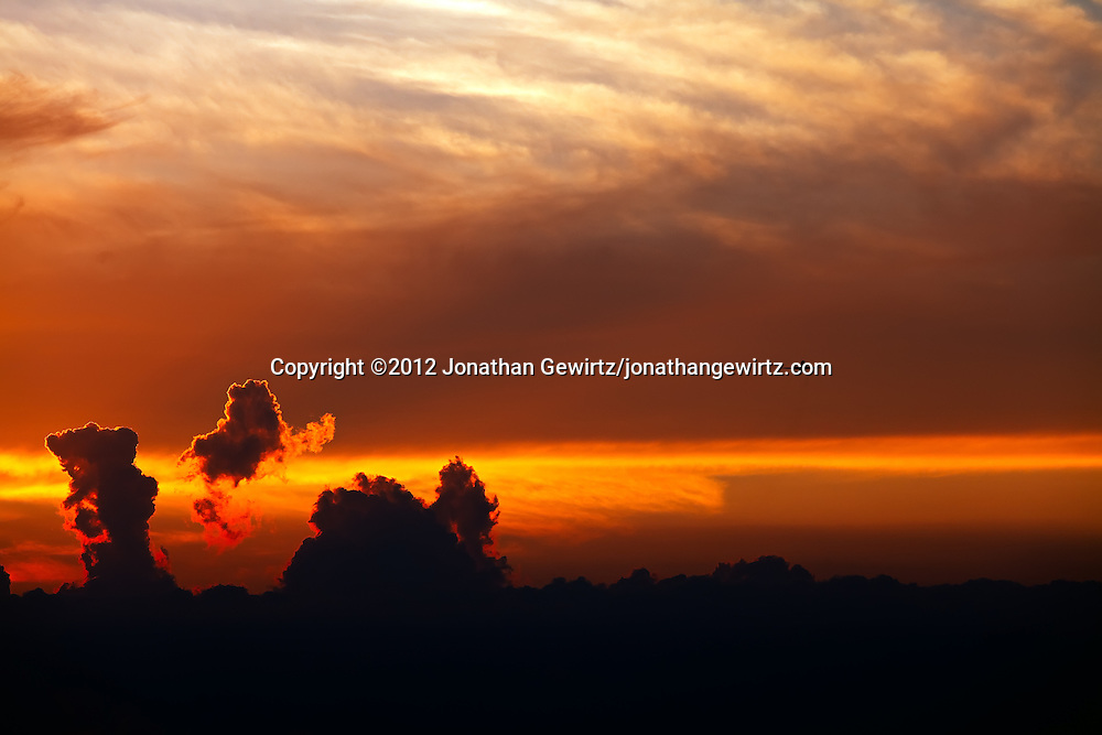 A distant jet aircraft climbs toward the camera above dramatically backlit clouds at sunset. WATERMARKS WILL NOT APPEAR ON PRINTS OR LICENSED IMAGES.