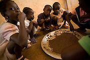 Children gather around a large plate of lentils during lunch in a classroom at the Idrissa Diouf primary school in Bignona, Senegal, on Tuesday June 12, 2007.