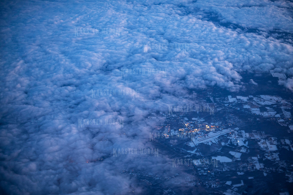 March 23, 2018 - U.S.A. : The lights of an unidentified snow-covered town are seen from the air, beyond a bank of clouds at dusk.  CREDIT: Karsten Moran / Redux