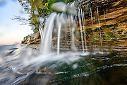 PICTURED ROCKS NATIONAL LAKESHORE - October 2016: Be prepared to get wet when photographing Elliot Falls, aka Miners Beach Falls, close up.  I like the splashes on the lens, though, as it adds a nice touch and reminds me that when I pushed the shutter I slipped and fell, sliding toward Lake Superior in Pictured Rocks National Lakeshore.<br />