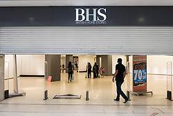 © Licensed to London News Pictures. 28/08/2016. London, UK. The shutters come down on the BHS store in Harrow, in north west London.  The Harrow store is one of the remaining 22 stores which closed for the last time today,  Shelves, fixtures and fittings are being sold as well as the last remaining stock.  After administrators, failed to find a suitable buyer for the department store chain, the decision was made to close all 164 shops, with the loss of 11,000 jobs. Photo credit : Stephen Chung/LNP