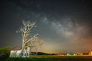 An old abandoned farm house stands, as if held by a tree that has grown with it, at the edge of an open field under a timeless expanse of stars and the Milky Way.