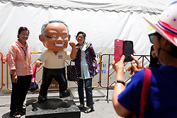 © Licensed to London News Pictures. 15/05/2014. PDRC supporters pose for a photo beside a cartoon statue of PDRC leader Suthep Thaugsuban at a protest site near the site of a grenade and gun shots attack at Democracy monument in Bangkok on May 15, 2014. Grenade blasts and gunfire rocked an anti-government protest site in Thailand's capital, leaving two dead and 24 wounded as fears of wider political violence mounted in Bangkok Thailand. Photo credit : Asanka Brendon Ratnayake/LNP
