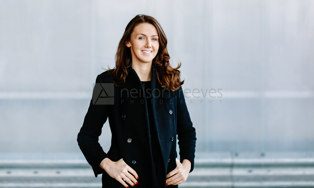 Corporate portrait taken outdoors with modern grey striped background features young business woman smiling