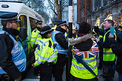 London, UK. 13th March, 2019. Pro-Brexit Yellow Vests UK activists complain to the Metropolitan Police after one of their number was detained inside the police vehicle in Westminster for questioning on the evening of the vote on a 'No Deal' Brexit in the House of Commons.