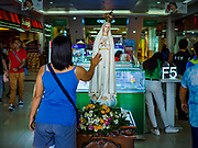 31 JANUARY 2018 - LEGAZPI, ALBAY, PHILIPPINES: People touch a statue of the Virgin Mary at the main entrance to the Pacific Mall in Lagazpi. The Philippines is the only Catholic majority country in Southeast Asia.        PHOTO BY JACK KURTZ