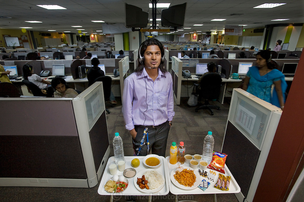 Shashi Kanth, a call center worker, with his day's worth of food in his office at the AOL call center in Bangalore, India. (From the book What I Eat: Around the World in 80 Diets.) He is 23 years of age; 5 feet, 7 inches; and 123 pounds. Like many of the thousands of call center workers in India, he relies on fast-food meals, candy bars, and coffee to sustain him through the long nights spent talking to Westerners about various technical questions and billing problems. He took a temporary detour into the call center world to pay medical and school bills but finds himself still there after two years, not knowing when or if he will return to his professional studies. MODEL RELEASED.