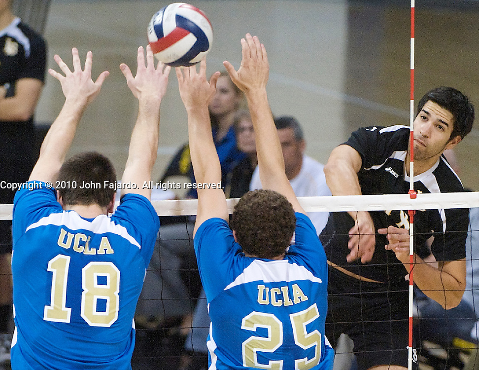 Dean Bittner(rear) hits over the block of Thomas Amberg(18) and Kevin Ker(25) in the Mountain Pacific Sports Federation match against UCLA at the Walter Pyramid, Long Beach Calif., Friday, April 9, 2010.
