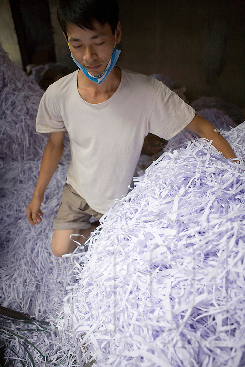 Workshop of recycling paper in the village of Cham Khe close from Hanoi. Vietnamese man carry recycled paper