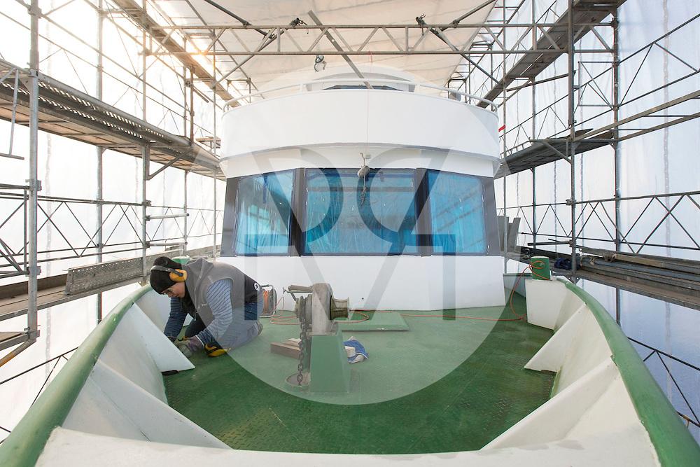 SCHWEIZ - MEISTERSCHWANDEN - Das Flaggschiff MS Brestenberg wurde über den Winter aus dem Wasser genommen und Renoviert. Hier schleift eine Mitarbeiterin die Farbe an, fuer den naechsten Anstrich - 10. Februar 2015 © Raphael Hünerfauth - http://huenerfauth.ch