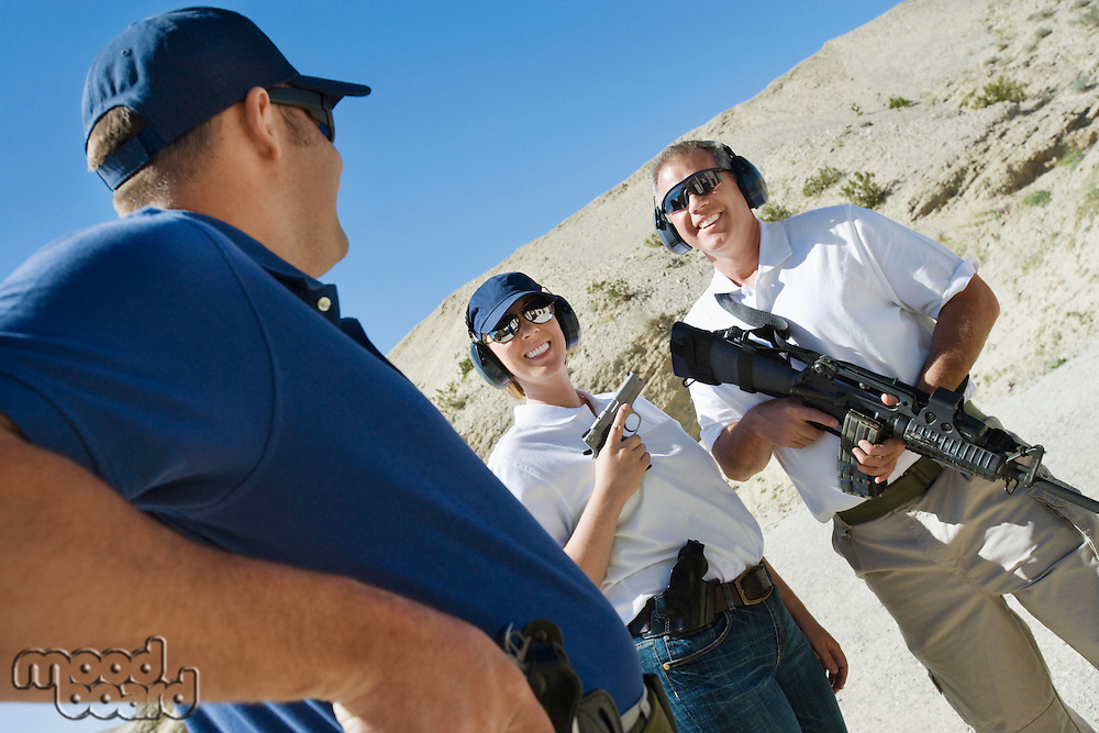 Instructor with couple at firing range in desert