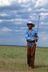 Cowboy playing golf in an open pasture