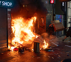 Hong Kong. 4 October 2019. Violent scenes in Hong Kong tonight with pro-democracy protestors vandalising shops and setting fire to the entrances of MTR stations. Protestors are angry with Chief Executive Carrie Lam's use of Emergency Powers to ban the wearing of masks during protests. Further demonstrations planned over the weekend. Pic; Fire started at Causeway Bay MTR station. Iain Masterton/Alamy Live News.