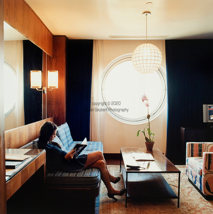 A woman reading in one of the suites available at the Maritime Hotel in the Chelsea area of Manhattan, New York City