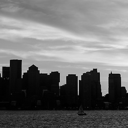 Panoramic Boston skyline black and white photo with downtown Boston city skyscraper buildings across Boston Harbor. Boston Massachusetts is a major American East coast city along the Atlantic Ocean in the United States.