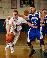 Laconia's Josh Emond and Winnisquam's Christian Serrano go after a loose ball during the semi final round at the 42nd annual Holiday Basketball Tournament Wednesday evening.  (Karen Bobotas/for the Laconia Daily Sun)