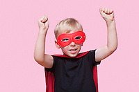 Young boy dressed in superhero costume with arms raised over pink background
