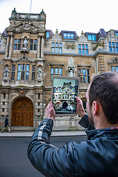 © Licensed to London News Pictures. 13/01/2016. Oriels College, Oxford. A man takes a picture of a Cecil Rhodes statue at Oriel College at Oxford University in Oxford. There is a campaign to remove the statue of Cecil Rhodes from the front of Oriel College by a group calling themselves Rhodes must fall. Photo credit : Mark Hemsworth/LNP