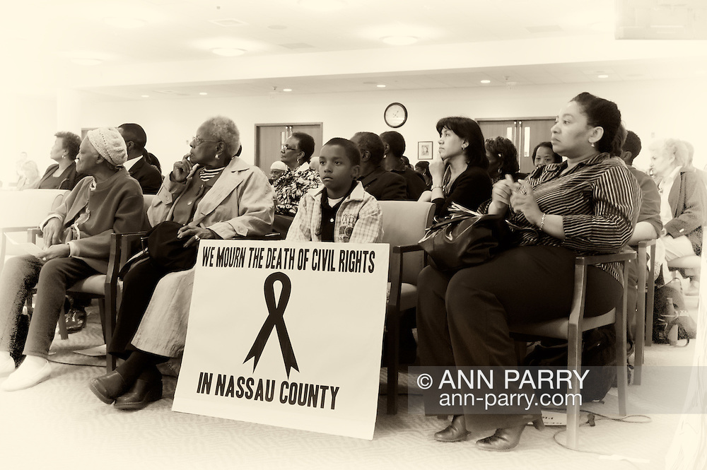 """May 9, 2011 - MINEOLA, NY:  Amid adults at public hearing, young Ramel Smith, Jr., sitting with sign: """"We Mourn the Death of Civil Rights in Nassau County."""" Front row, first left is Golena White of Hemptead. Nassau County Legislature's public hearing on Legislative Redistricting, at Nassau County Executive and Legislative Building, 1550 Franklin Avenue, Mineola, Long Island, New York, USA."""