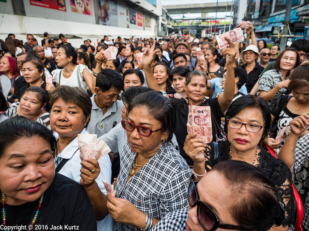 11 NOVEMBER 2016 - BANGKOK, THAILAND:  Thais waiting to buy rice from Yingluck Shinawatra hold up the Thai Baht they were using to pay for the rice. Yingluck Shinawatra, the former Thai Prime Minister deposed in a coup in 2014, has started selling rice directly to Thai consumers. She buys the rice from farmers at market prices and then sells it to urban consumers at the price she paid. She said she's doing it to help out farmers, who are trying to deal with depressed prices. Yingluck is facing prosecution on corruption related charges going back to a rice price support scheme her government used to try to help farmers in 2011 and 2012. Even after the coup, she is still personally popular and hundreds of people showed up to see her at the rice distribution point at a mall in Samut Prakan province, in suburban Bangkok.  PHOTO BY JACK KURTZ