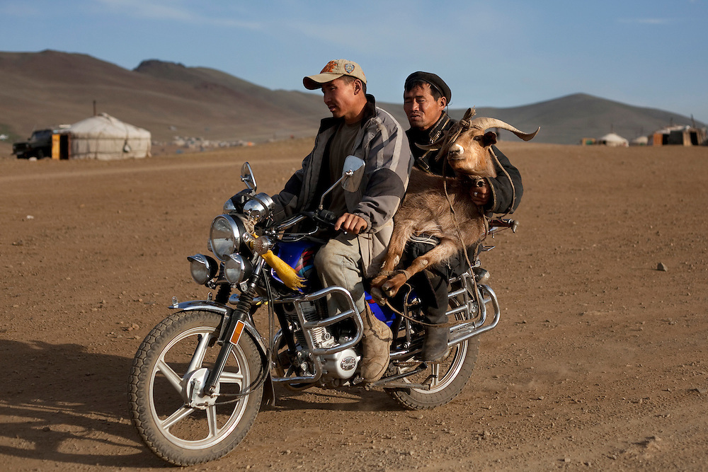 Ninja miners carry a ram by motorcycle through a gold mining camp.