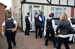 © Licensed to LondonNews Pictures. 09/10/2013<br /> London, England. 9/10/2013 Police officers from The City of London Police force execute a warrant in Morden, SW London.<br /> <br />   Insurance fraud detectives as they execute 28 warrants across the country (London, Leicestershire, Manchester, Thames Valley, West Midlands) in dawn raids on Wednesday (9th October 2013).<br />  <br />  168 police officers are involved in this operation which is the culmination of months of investigation by detectives from the City of London Police's Insurance Fraud Enforcement Department (IFED) into people selling fake motor insurance, a practice commonly known as 'ghost broking'.<br /> <br /> Ghost brokers often target young drivers by offering cheap deals but anyone who buys a ghost broker policy is driving without insurance and without valid insurance they risk their car being seized by police as well as fines, penalties and a criminal record.. Photo credit : Mike King/LNP