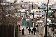 Oyuntsetseg (second from left) and Regzen Batsuuri (right) and their two children, Khorloo (17, left) and Batbileg (12, second from right) visit the neighborhood where they once lived in Ulaanbaatar, Mongolia. They hadn't been back there since they lost the property. [Although property in this case is a misnomer. They owned the structures, but were squatters on the land as is everyone in the settlement because ownership of private land is not allowed in Mongolia. Land belongs to the government --2001]. From coverage of revisit to Material World Project family in Mongolia, 2001.