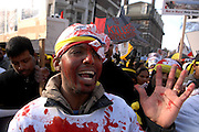A young man covered in fake blood calls for the British Government to intervene in the Sri Lankan conflict
