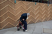 An elderly pensioner struggles to his feet using a four-wheeled rollator mobility aid past the zigzag battens of a construction hoarding at Notting Hill, on 13th March 2018, in London, England.