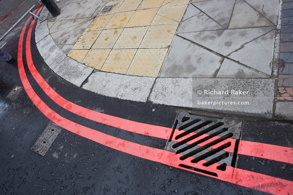 Double red curved lines around the kerbside of a London Street.