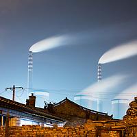 China, Shanxi Province, Datong, Towering smokestacks from coal-fried Datong No. 2 Power Station behind brick walls of old neighborhood at night
