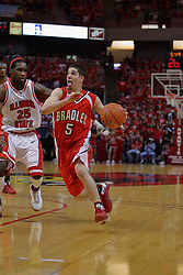 "31 January 2009: Sam Maniscalco heads for the lane defended by Champ Oguchi. The Illinois State University Redbirds join the Bradley Braves in a tie for 2nd place in ""The Valley"" with a 69-65 win on Doug Collins Court inside Redbird Arena on the campus of Illinois State University in Normal Illinois"