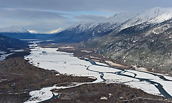 The Chilkat River valley outside Haines, Alaska is a popular destination for photographers who come to the river in November and December to photograph one of the largest gatherings of bald eagles in the world. This aerial photo is looking up the river valley from Haines to the Alaska Chilkat Bald Eagle Preserve and further to the border with Canada. Four Winds Mountain is located on the left and the Takshanuk Range on the right.
